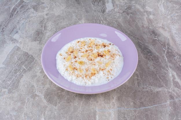 Um prato roxo cheio de mingau de aveia saudável com canela em pó