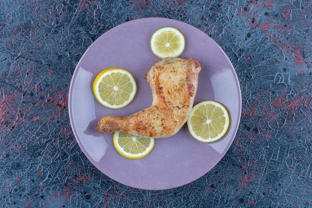 Um prato roxo com carne de coxa de frango com rodelas de limão.