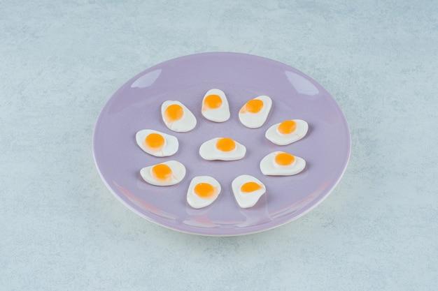 Um prato roxo de doces de geleia de ovos mexidos na superfície branca
