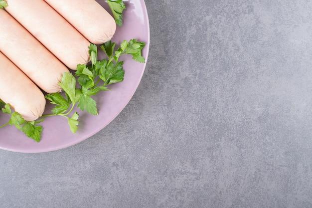 Um prato roxo de salsichas cozidas com salsa
