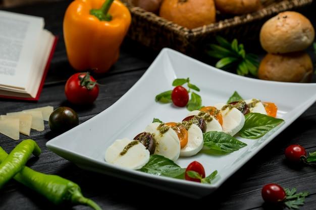 Um prato suqare de queijo mozarella picado, cerejas e folhas de hortelã.
