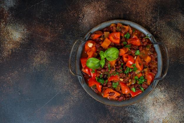 Um prato tradicional caucasiano, lobio de feijão vermelho com legumes e ervas em uma bandeja de lata fica em uma mesa de concreto à direita. ensopado vegetariano de feijão, pimentão e ervas. orientação horizontal. t