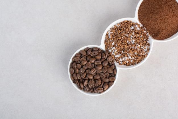 Um prato três branco cheio de grãos de café e cacau em pó
