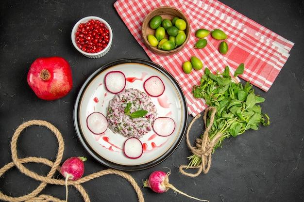 Um prato um prato de sementes avermelhadas de frutas cítricas de romã verde