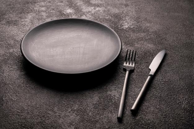 Um prato vazio preto fosco e uma faca e um garfo. um conceito para a decoração do restaurante.