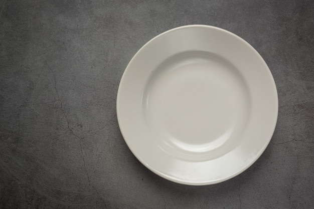 Um prato vazio redondo branco na superfície escura