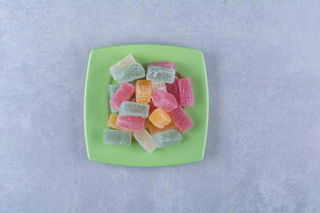 Um prato verde cheio de balas de gelatina açucaradas na superfície cinza