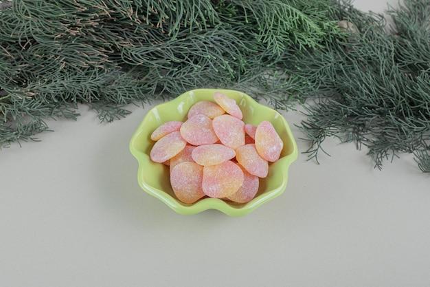 Um prato verde cheio de balas de gelatina em forma de coração.