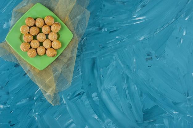 Um prato verde com hambúrgueres gelatinosos em uma superfície azul