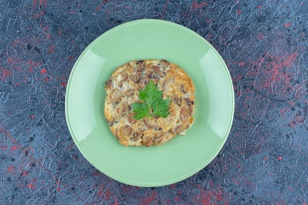 Um prato verde com ovo frito e carne.