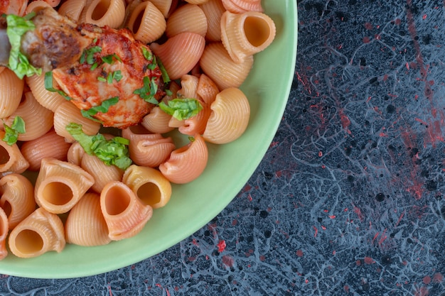 Um prato verde com pernas de frango frito com macarrão.