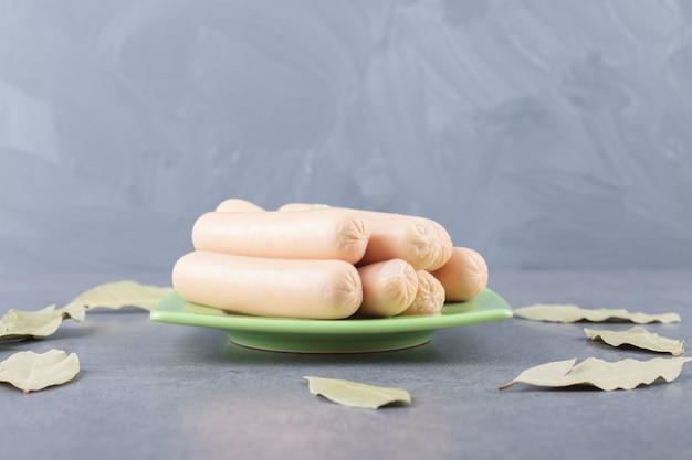 Um prato verde com salsichas cozidas e folhas de louro