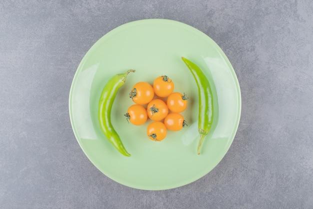 Um prato verde com tomate cereja e pimenta malagueta