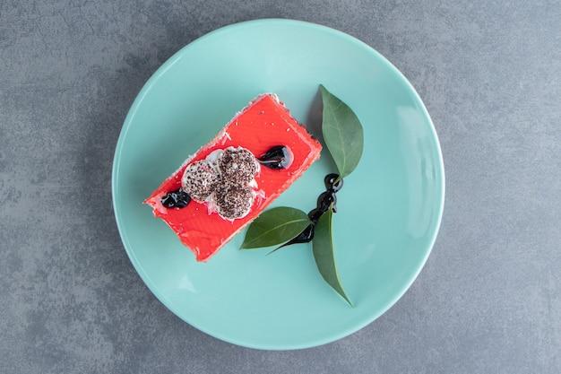 Um prato verde com um pedaço de bolo cremoso e folhas