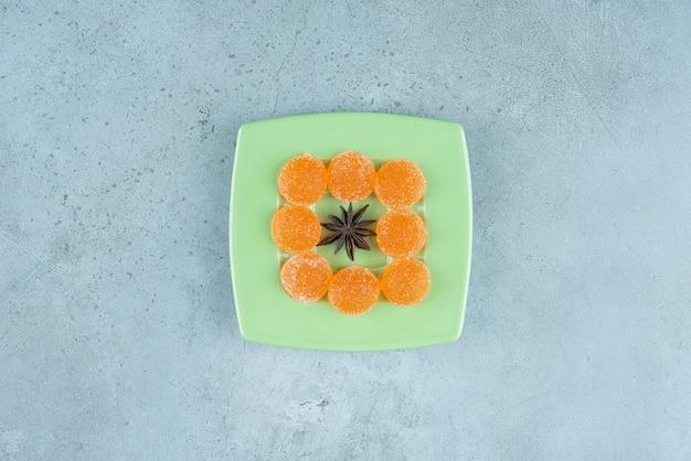 Um prato verde de anis estrelado e geleias de laranja.