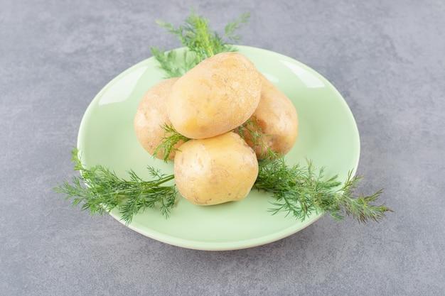 Um prato verde de batatas cruas com endro fresco