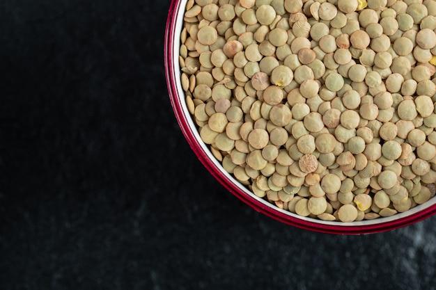 Um prato vermelho com lentilhas não preparadas em um preto.
