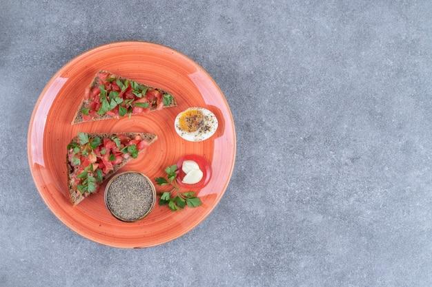 Um prato vermelho com ovo cozido e torradas