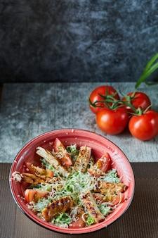 Um prato vermelho com salada caesar e tomates na superfície de mármore