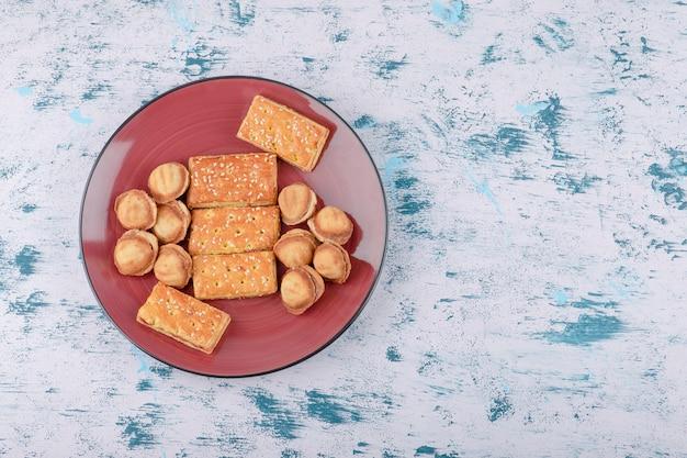 Um prato vermelho de nozes de shortbread com leite condensado e biscoitos.