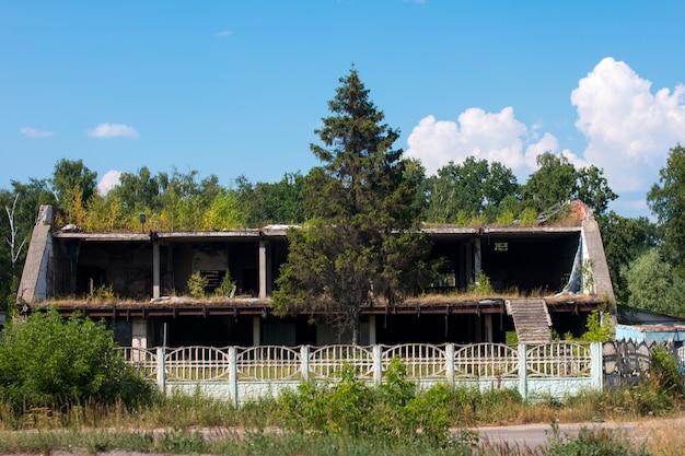 Um prédio abandonado e inacabado. canteiro de obras coberto de mato de dois andares