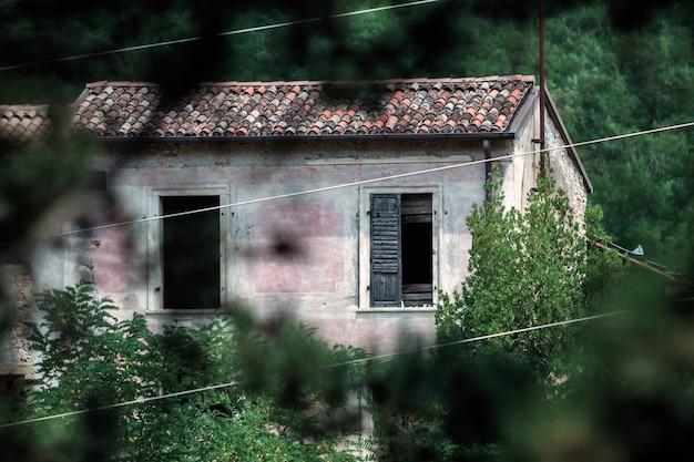 Um prédio abandonado nas árvores com uma janela aberta e outra entreaberta