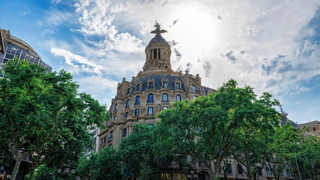 Um prédio antigo feito em estilo clássico, com vegetação em barcelona, espanha