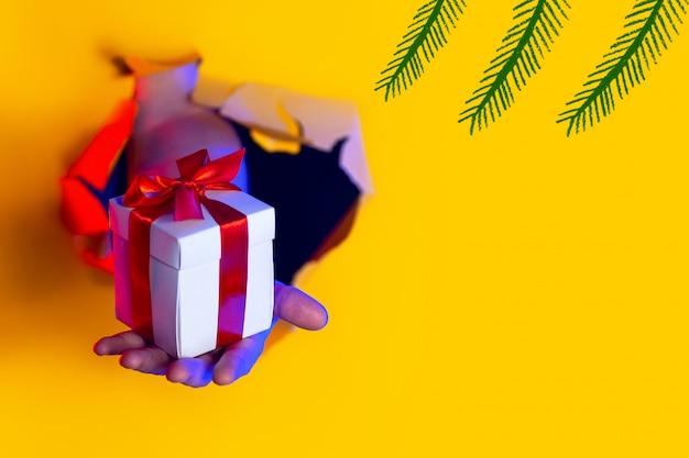 Um presente com um laço vermelho na mão surge de um buraco irregular no fundo de papel amarelo, iluminado pela luz neon