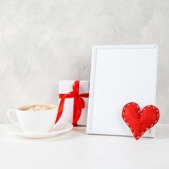 Um presente, coração vermelho, café da manhã contra o de uma parede de luz, conceito, um cartão postal para o dia dos namorados.