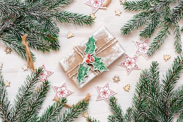 Um presente de ano novo em um fundo de madeira, juntamente com galhos de pinheiro e decorações.