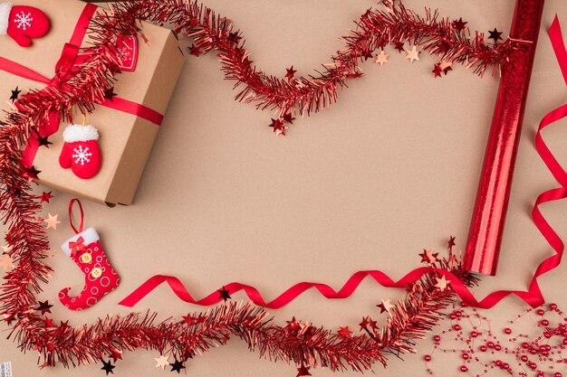 Um presente de papel kraft localizado entre enfeites vermelhos festivos, fita vermelha encaracolada, pequenas luvas decorativas e uma meia para doces. bom espírito. espírito de natal. isolado