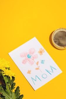 Um presente de uma criança para o dia das mães, um cartão de uma foto e um café com flores