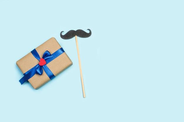 Um presente e um bigode em um fundo azul claro