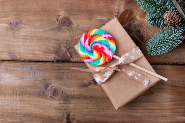 Um presente em papel cinza está amarrado com uma fita dourada e um pirulito com listras brilhantes. sobre um fundo de madeira