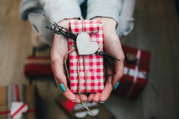 Um presente em suas mãos, muitos no chão Foto gratuita