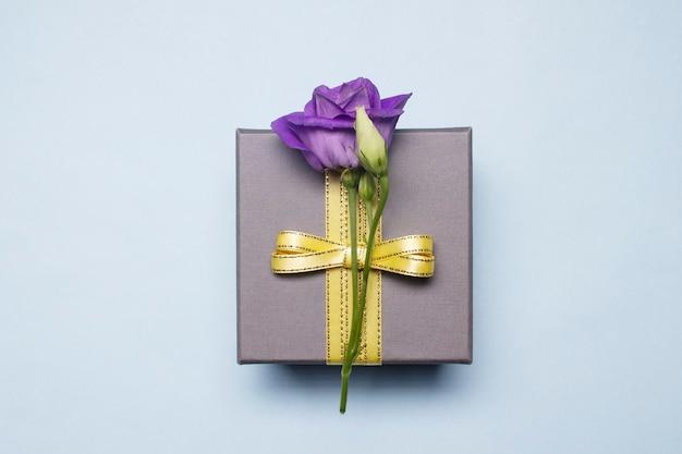 Um presente em uma caixa de prata com uma flor amarrada com uma fita dourada em um fundo branco