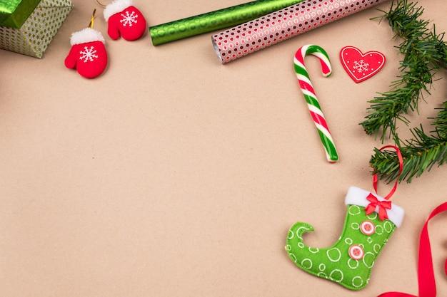 Um presente em uma embalagem brilhante, localizada em um fundo bege, no qual há rolos de papel brilhantes, pequenas luvas, galhos de pinheiro, uma bota, uma fita encaracolada, um brinquedo de natal.