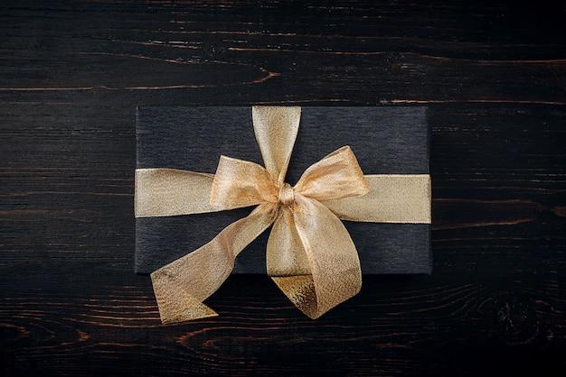 Um presente embrulhado em papel preto e amarrado com uma fita de ouro. conceito de presente caro.