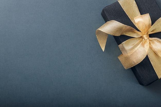 Um presente embrulhado em papel preto e amarrado com uma fita de ouro.