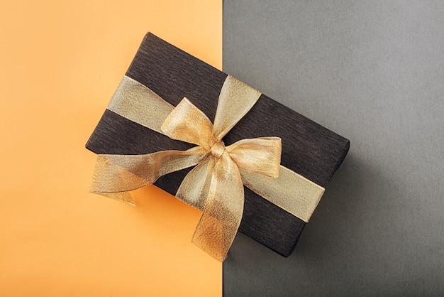 Um presente embrulhado em papel preto e amarrado com uma fita dourada