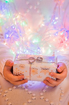 Um presente embrulhado em uma embalagem festiva nas mãos de uma criança em um suéter branco de malha