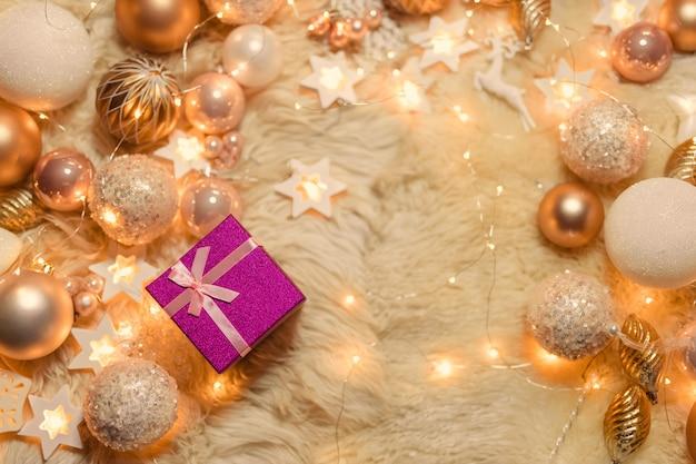 Um presente entre brinquedos de natal dourados e rosa e luzes de guirlanda. camada plana, vista superior, espaço de cópia.