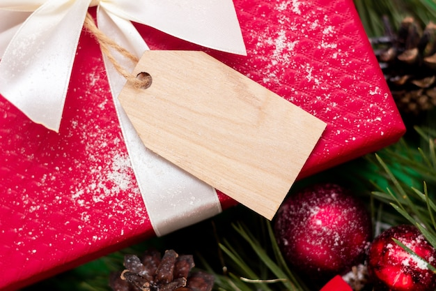 Um presente vermelho com um formulário em branco de madeira para o texto um galho de uma árvore de abeto decoração de natal e ano novo