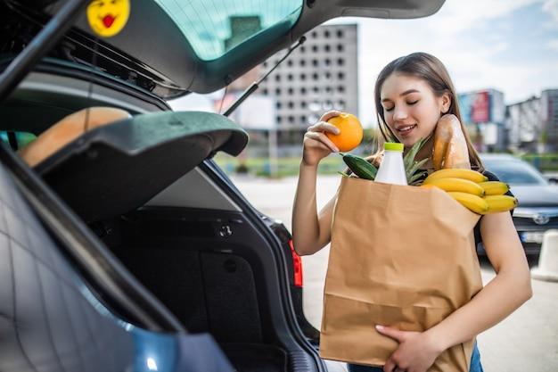 Um processo de jovem levando mantimentos de um supermercado do carrinho para o caminhão