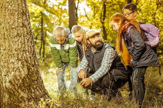 Um professor alegre mostrando o chão da floresta para seus alunos em um belo dia