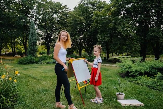 Um professor dá aula para crianças em um parque ao ar livre. de volta à escola, aprendendo durante a pandemia.