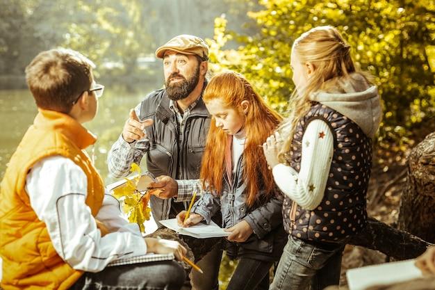 Um professor de bom coração ensinando seus alunos na floresta em um bom dia