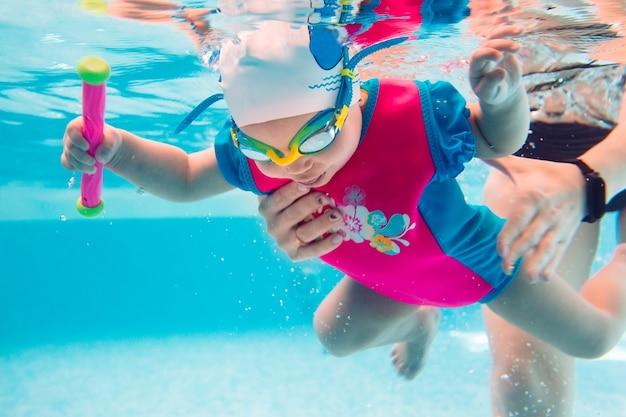 Um professor de natação ensina uma criança a nadar na piscina.