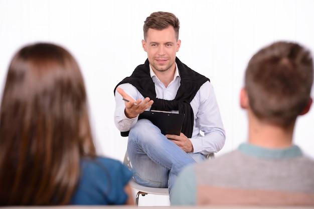 Um psicólogo masculino discute problemas de casal em uma sala.