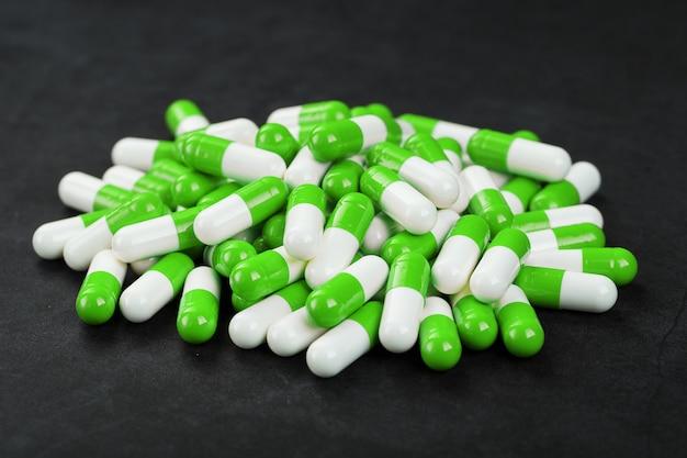 Um punhado de cápsulas de comprimidos verdes e brancos sobre um fundo preto. produtos farmacêuticos, remédios, vitaminas, drogas, ecstasy